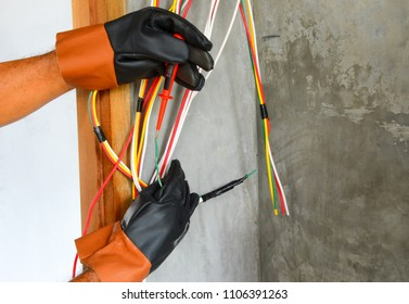 Electricians are using a screwdriver to test electrical current for safety while installing electrical systems in a building.