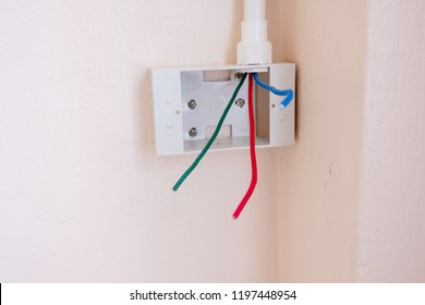 Electricians are walking the electrical system and storing electrical wires coming out of the PVC pipe into a PVC white box that is used to store electrical wiring, especially for security purposes.
