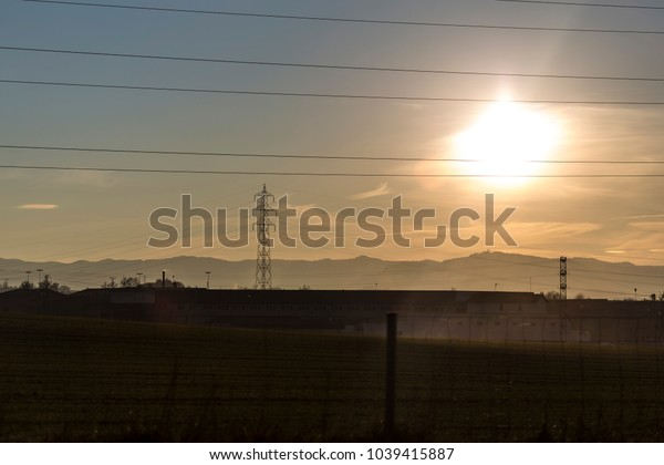 Electricity cables and towers silhouettes on a sunshine landscape