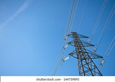 Electricity concept, Close up high voltage power lines station. High voltage electric transmission pylon silhouetted tower. Blue sky and low angle view