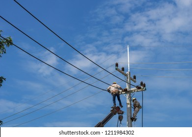 Electricity concept,Electricians Technician with hardhat and safety uniform checking repairing fixing electric wire on power pole.high voltage power lines and blue sky background.