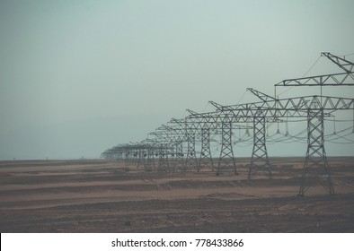 Electricity distribution stations. Electric energy transmission. Ecology, eco power, technology concept. Power line towers in desert on blue sky background. Global warming, climate change.