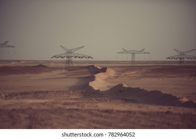 Electricity distribution stations. Power line towers in desert on grey sky background. Global warming, climate change. Electric energy transmission. Ecology, eco power, technology concept.