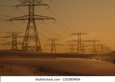 Electricity or energy industry, high voltage lines and towers in desert at sunset