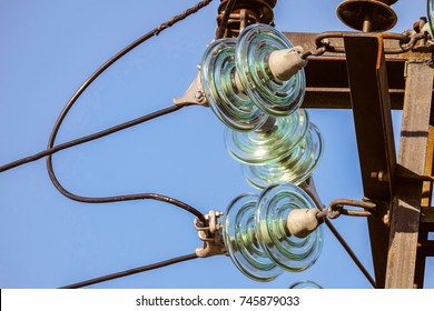 Electricity garlands close-up of insulators with electric wires on a top steel mast support