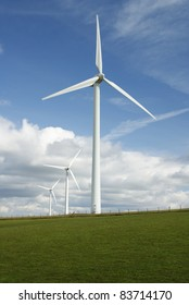 Electricity generating wind turbines on a rural green hillside with a blue sky and white clouds in the background in the UK