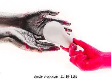 Electricity, light. Concept of helping each others. Close up of hand colored in pink giving bulb and sharing the light with grey ones. People always need help and support. Two people share light