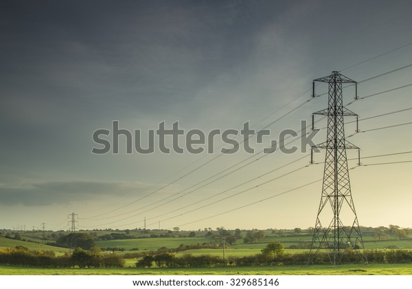 Electricity lines carrying power across the countryside of England as the evening sun begins to set.