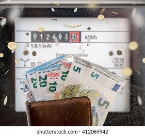 electricity meters and a wallet with euro banknotes and coins / electricity meters