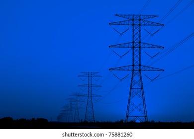 Electricity pillars against blue sky