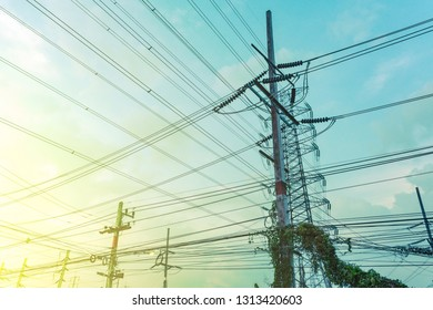 Electricity pole with silhouette sunset sky, Electricity pylon with shadow of tree in dawn time, Electricity power transmission line on sunset with copy space, Electricity pylon on orange sky