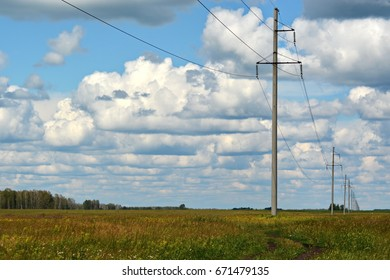 the electricity poles on the field outside of town, under a cloudy sky