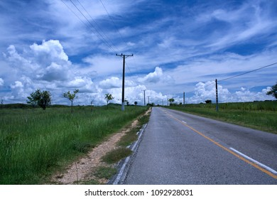 Electricity poles standing near narrow road going through green fields of countryside in Trinidad, Cuba.
