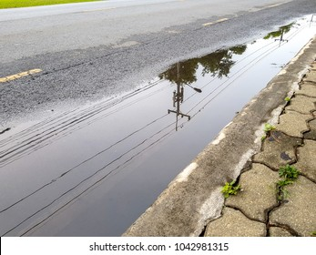Electricity post and line reflect on the water-logged on the street.