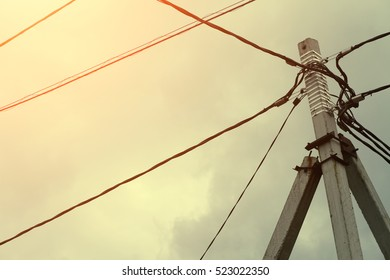Electricity power pole with many wires against the backdrop of sunset or dawn sky.