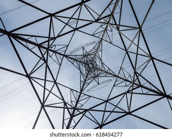 Electricity pylon abstract. Abstract view looking up at the construction of a UK electricity pylon with clear sky background.