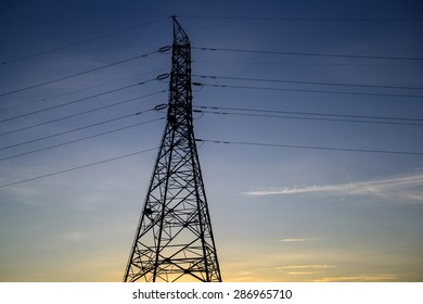 Electricity pylon against blue sky and dusk sunset