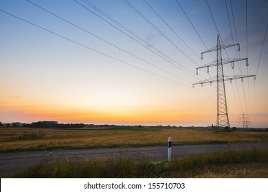 Electricity pylon against sunset blue hour with street