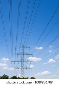 Electricity pylon in front of blue sky with light clouds.