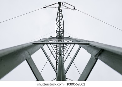 Electricity pylon pole post, shot from the ground up, high voltage metal construction with electric wires and cables, against a blown out white sky, geometric shape and pattern