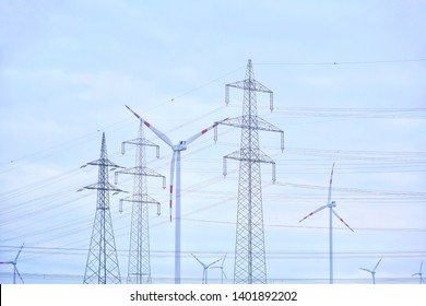 Electricity pylon with power lines and wind mill turbines on blue sky background. Silhouette of power transmission tower and electricity wind stations. High voltage tower with wind turbine generator