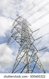 Electricity pylon silhouetted against blue sky wih cloud background. High voltage tower