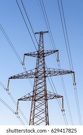 Electricity pylon silhouetted against blue sky sunshine background. High voltage tower