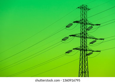 Electricity pylon silhouetted against green sky background. High voltage tower