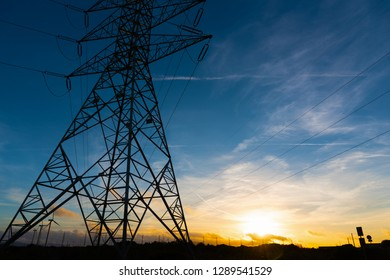 Electricity pylon under a colorful sky at sunset. Sardinia, Italy