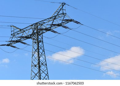 Electricity pylon with wires in front of blue sky with white clouds