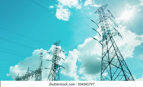 Electricity pylon,Electricity tower station with cloudy and sun over blue sky