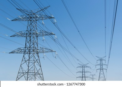 Electricity pylons against a blue sky.