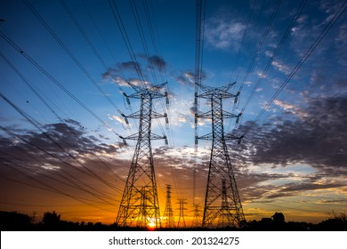 Electricity pylons and cable lines during sunset. Horizontal format