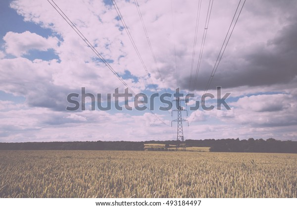 Electricity pylons going across fields in the English countryside Vintage Retro Filter.