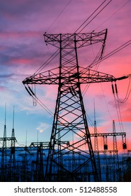 Electricity pylons and lines at dusk at sunset