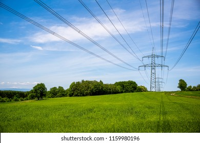 electricity pylons on a green meadow