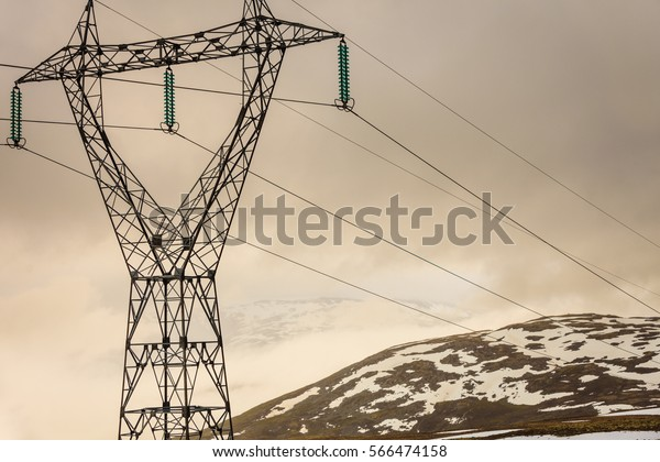 Electricity pylons power lines high voltage towers in norwegian mountains landscape, hazy rainy day, hiking area between Aurland and Lærdal in Norway