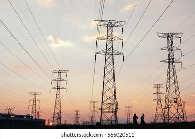 Electricity pylons and power lines, at sunset. warm tone one applied for a futuristic look