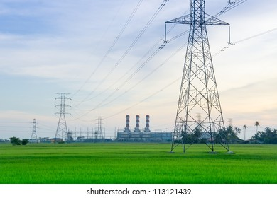 Electricity pylons with  power plant at the horizon