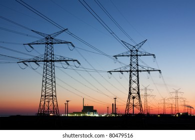 Electricity pylons at sunset with nuclear power plant at the horizon