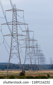 Electricity pylons or transmission towers carrying high voltage power lines and overhead cables above land as part of the national grid network supplying power to peoples homes and businesses