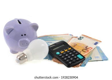 Electricity spending concept with a piggy bank next to a wad of banknotes and a calculator on a white background