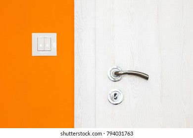 Electricity switch in a modern bright orange wall alongside a white wooden door with metal handle and keyhole in a modern home in a close up architectural background view