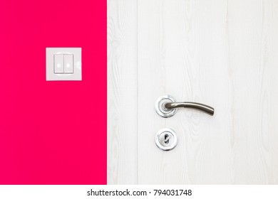 Electricity switch in a modern bright raspberry red wall alongside a white wooden door with metal handle and keyhole in a modern home in a close up architectural background view