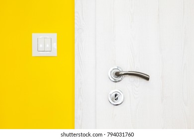 Electricity switch in a modern duck yellow wall alongside a white wooden door with metal handle and keyhole in a modern home in a close up architectural background view