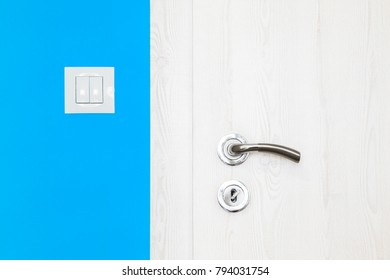 Electricity switch in a modern mediterranean light blue wall alongside a white wooden door with metal handle and keyhole in a modern home in a close up architectural background view