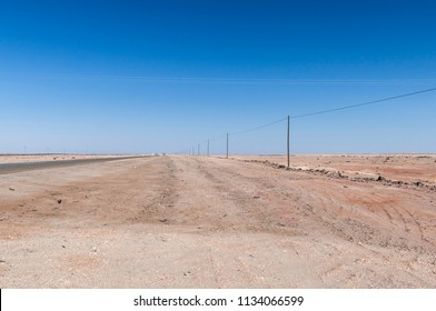 Electricity track in the desert in a straight line to the horizon, Namibia, Africa. / Electricity track in the Namib Desert