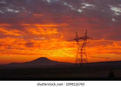 Electricity transfer lines and a pylon at sunrise