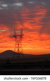 Electricity transmission lines and a high voltage pylon in sunrise