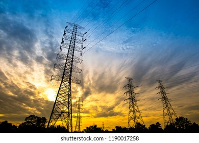 Electricity transmission power tower over sunset sky background